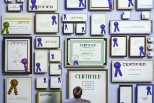 Businessman staring at certificates on wall